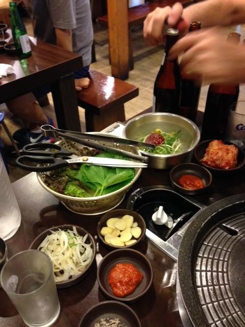 God middag, barbecue vid bordet där man grillar kött och äter i salladsblad.