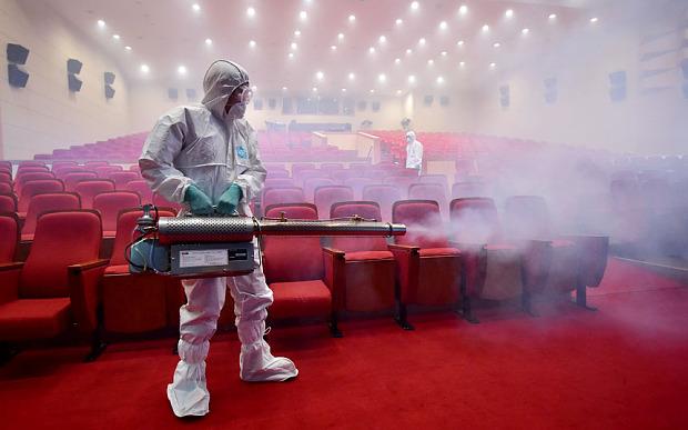 En teater sprayas för att desinfekteras. Alla bör använda sprit för händerna efter hosta/nysning,